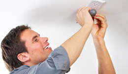 Man replacing the cover of an electrical outlet on the ceiling